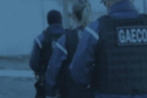Três integrantes MPPR, de costas, com coletes com a identificação do Gaeco.